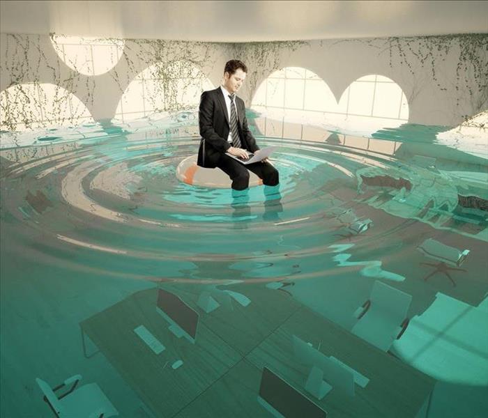 suited man sitting on tube in flooded office
